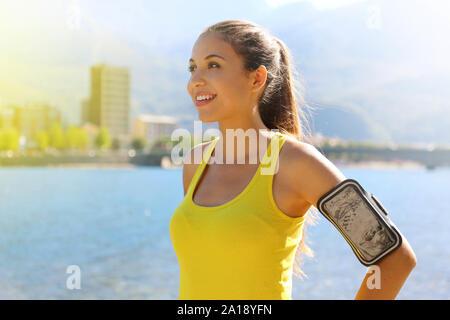 Femme de remise en forme avec la bande de bras pour faire l'exécution de la technologie téléphonique exercice marathon jogging chaud d'étirement le matin dans le lac de la ville. Banque D'Images
