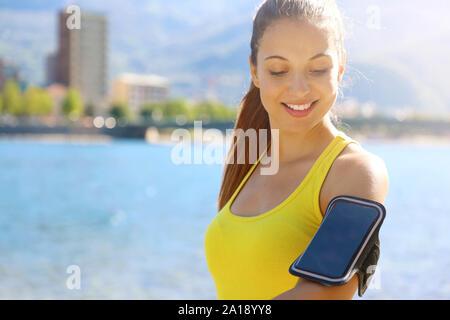 Femme de remise en forme avec la bande de bras pour faire l'exécution de la technologie téléphonique exercice marathon jogging stretching réchauffer le matin dans le lac de la ville. Copier l'espace. Banque D'Images