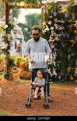 Asiatique barbu père avec enfant en poussette dans le parc. Banque D'Images