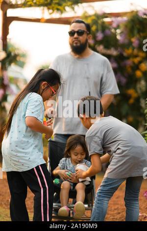 La famille asiatique dans le parc. Tout-petit frère de potable. Banque D'Images