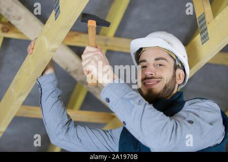 Roofermaker heureux à l'aide d'un marteau dans une construction traditionnelle Banque D'Images