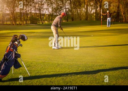 Deux golfeur aîné jouer au golf au crépuscule.