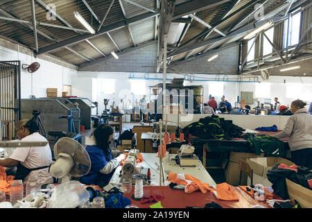 Les femmes utilisant des machines à coudre et du tissu de tri dans une usine de confection Banque D'Images