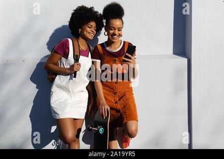 Deux femmes en utilisant smartphone avec skateboard Banque D'Images