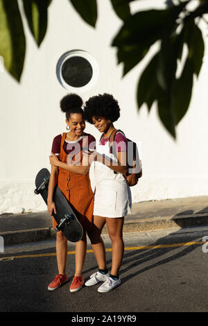 Deux femmes avec skateboard using smartphone Banque D'Images