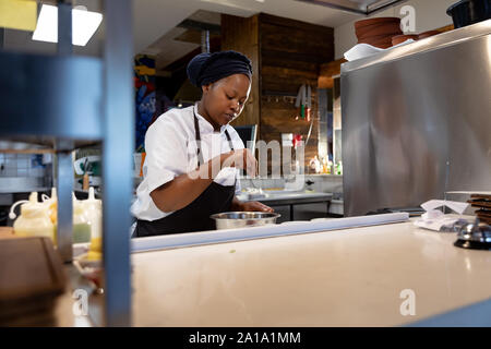 Woman cooking in restaurant kitchen Banque D'Images
