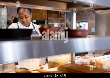 Woman working in restaurant kitchen Banque D'Images