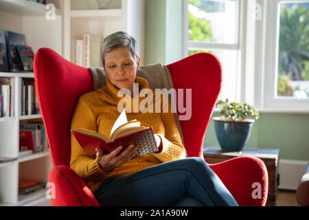 Femme mature seule à la maison, reading book