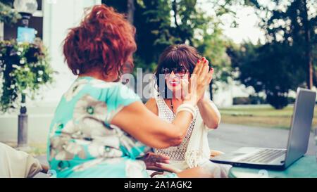 Happy female friends sont haute donnant cinq, célébrons les succès tandis qu'à l'autre assis dans la table d'un café en plein air.