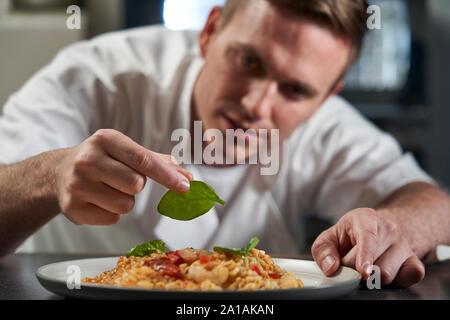 Male Chef Garniture assiette de nourriture dans la cuisine professionnelle Banque D'Images