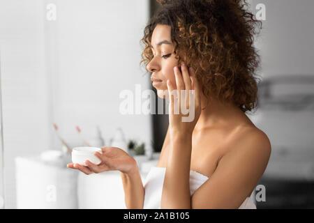 Black Woman Holding pot de crème visage debout dans salle de bains Banque D'Images