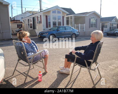 Deux femmes se relaxer sur des chaises pliantes à une remorque du New Jersey et cottage site et bénéficiant d'un soleil de fin d'été. Banque D'Images