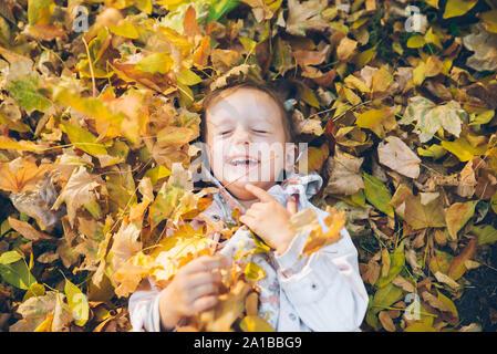 Little girl portant sur le terrain dans des feuilles jaunes
