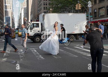 Un modèle d'une robe nuptiale pose pour des photos sur un coin de rue animée - 7th Ave. et West 29th Street - à Manhattan, New York City. Banque D'Images