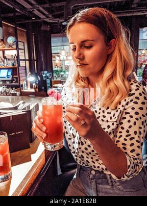 Femme dans la vingtaine portant chemise imprimer dalmate dans un bar, boire un cocktail