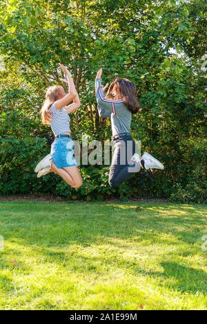 Deux adolescents Jeunes filles sautant dans un parc en été. S'amuser en vacances. Heureux les amis de passer du temps ensemble. L'amitié. Banque D'Images
