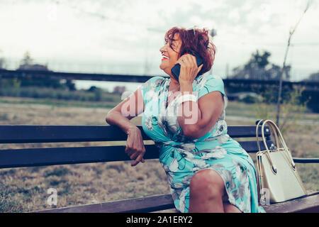 Belle femme Senior est l'appel sur un téléphone cellulaire et de parler tout en restant assis sur un banc