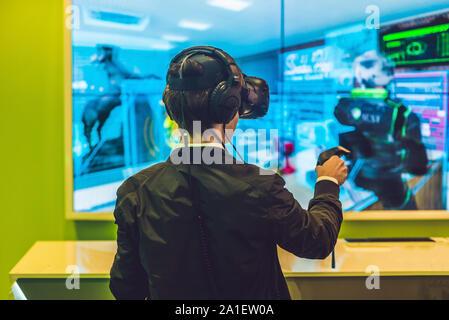 Jeune homme jouant des jeux vidéo lunettes de réalité virtuelle. Cheerful man s'amusant avec les nouvelles tendances de la technologie - concept de jeu. Banque D'Images