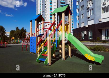 En bois coloré vide children's slide avec échelle sur l'aire de jeux. Attraction touristique situé dans la cour contre l'immeuble de grande hauteur et de ciel bleu.