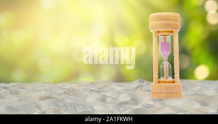 Jeu de Hourglass sur un fond de sable blanc, fond vert naturel, concept de temps Banque D'Images