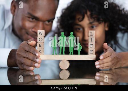 Jeune couple La protection du travail et la vie personnelle sur Seesaw Banque D'Images