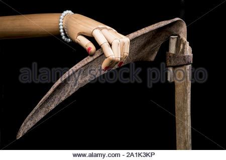 Main de mort posée sur sa faux. Sur fond noir. Avec copie espace texte. Studio Shot. Banque D'Images