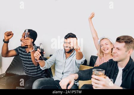 Loisirs, sport, concept de bonheur. Happy friends regarder match de foot à la télé assis sur table avec boissons, élever les mains, à crier, à la célébration de but Banque D'Images