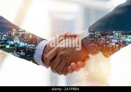 Partenariat. double exposition de droit de l'homme d'affaires avec les investisseurs et les partenaires pour faire face aux succès de la réunion pendant le lever du soleil et la ville Banque D'Images