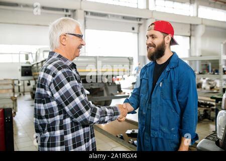 Heureux jeune réparateur de barbus maintenance service client mature salutation par handshake in workshop Banque D'Images