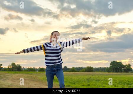 Jeune fille en marche avec sac à dos jaune, avec les mains ouvertes, fond nature prairie ciel dramatique, soirée sunset sky