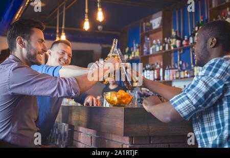 Heureux les gars de trinquer les bouteilles de bière dans Bar Banque D'Images