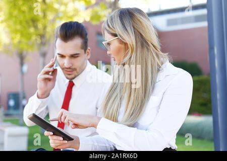 Young businesswoman showing comprimé à l'homme d'affaires occupé lors de l'appel à l'extérieur Banque D'Images