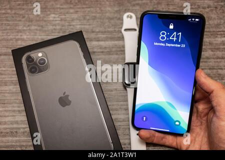 Homme tenant un nouvel iPhone 11 Pro avec une boîte sur la table avec Apple Watch.