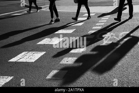 Image en noir et blanc des silhouettes d'un groupe de piétons non reconnus les personnes qui traversent une route Banque D'Images