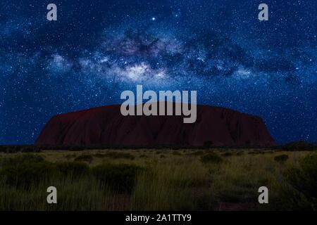 Uluru spectaculaire par nuit avec voie lactée, les étoiles et les galaxies de champ. Le Parc National d'Uluru-Kata Tjuta en Territoire du Nord, Centre de l'Australie. Banque D'Images