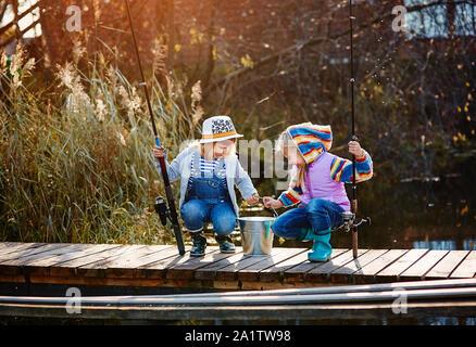 Deux petites filles avec des cannes à pêche, assis sur un ponton en bois et la vantardise de poisson frais. Banque D'Images