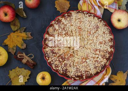 Tourte aux pommes est situé dans une forme en céramique sur un fond sombre, vue du dessus, close-up, l'orientation horizontale Banque D'Images