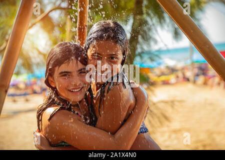 Portrait de deux petites filles se tenant ensemble sous une douche extérieure sur la plage, les meilleurs amis avec plaisir de passer des vacances d'été près de la mer