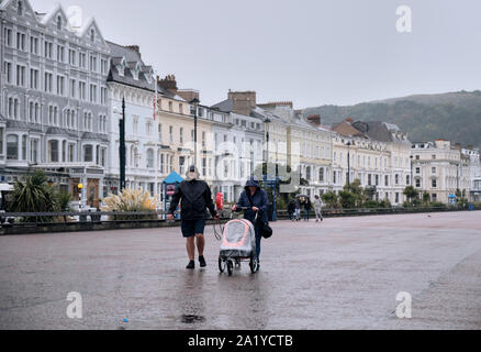 En quelques vêtements de pluie poussant un landau, une marche sous la pluie sur l'esplanade à Llandudno Pays de Galles sur un jour d'automne gris Banque D'Images