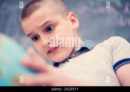 Happy cute boy apprentissage du monde en utilisant globe de terre alors qu'il se tenait devant le tableau noir Banque D'Images