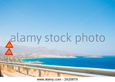 Belle vue sur la mer depuis la fenêtre de voiture. La signalisation routière et des clôtures sur la route. Grèce, Crète, Elounda. Banque D'Images