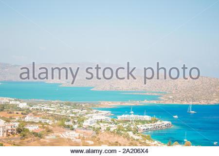Bleu de la mer de rochers et l'île de Kalydon en face. Lassithi, Elounda, Grèce. Magnifique baie avec les bateaux. Banque D'Images