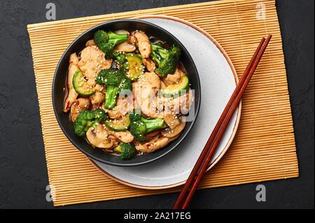Poulet au Hunan bol noir dark slate à fond. Poulet Hunan est chinois ou l'indo-chinoise plat à emporter avec brocoli, courgettes, shiitake Banque D'Images