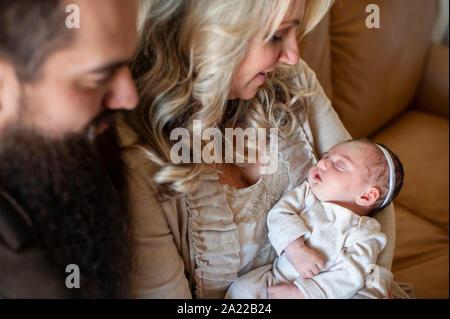 Mère et père à regarder leur bébé nouveau-né fille sur le canapé à la maison Banque D'Images