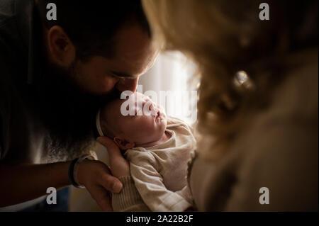 Father kissing filles nouveau-né endormi dans les bras de la mère de la tête