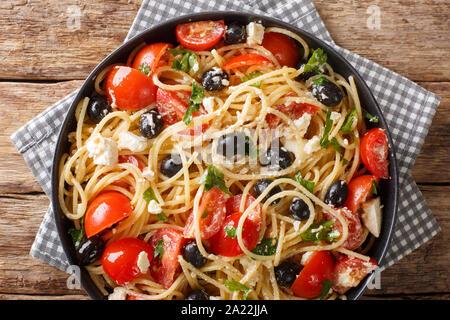 Pâtes salade grecque traditionnelle spaghetti avec fromage, olives, tomates close-up sur une plaque sur la table. Haut horizontale Vue de dessus