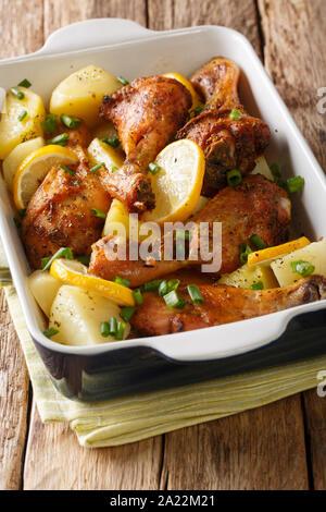 Poulet grec avec du citron et des pommes de terre bouillies close-up dans un plat allant au four, sur la table verticale. Banque D'Images