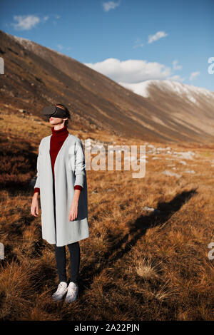 Femme dans la réalité virtuelle. Paysage de montagne à l'arrière-plan.