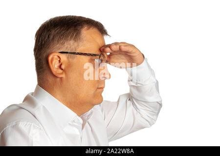 Un homme âgé en protégeant ses yeux du soleil avec sa main se penche sur la distance. Banque D'Images