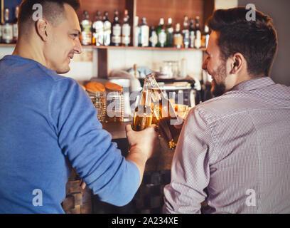 Deux gars gai de s'amuser ensemble dans un pub, tintement des bouteilles de bière, l'espace vide, vue arrière Banque D'Images